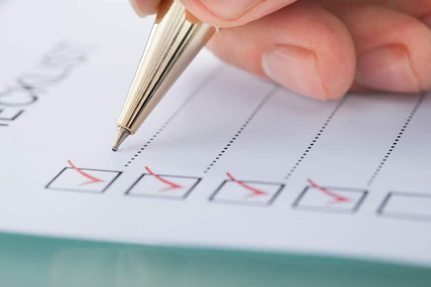 29529383 - cropped image of businessman preparing checklist at office desk