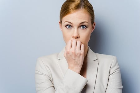 37821985 - a little bit nervous. nervous young businesswoman biting her nails while standing against grey background